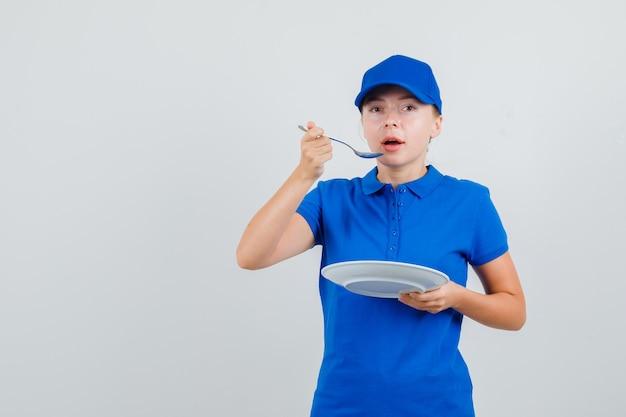 Lieferfrau, die mit löffel im blauen t-shirt und in der kappe isst Kostenlose Fotos