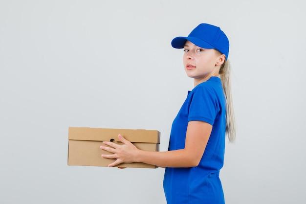 Lieferfrau, die pappkarton im blauen t-shirt und in der kappe hält und zuversichtlich schaut. Kostenlose Fotos