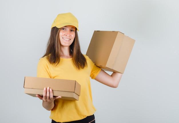 Lieferfrau, die pappkartons hält und im gelben t-shirt, in der hose und in der kappe lächelt Kostenlose Fotos