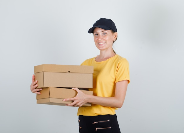 Lieferfrau, die pappkartons im t-shirt, in der hose und in der kappe hält und glücklich schaut Kostenlose Fotos