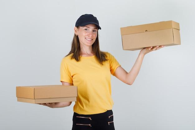Lieferfrau, die pappkartons im t-shirt, in der hose und in der mütze hält und fröhlich schaut Kostenlose Fotos