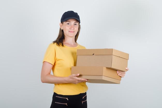 Lieferfrau, die pappkartons im t-shirt, in der hose und in der mütze hält und lustig schaut Kostenlose Fotos