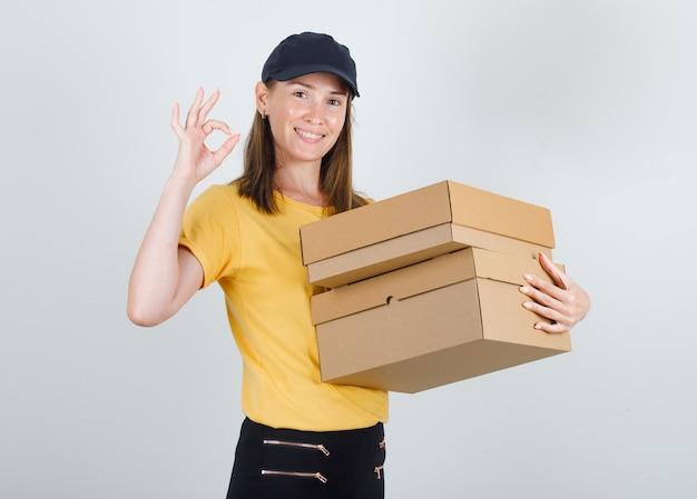 Lieferfrau, die pappkartons mit ok-zeichen im t-shirt hält Kostenlose Fotos