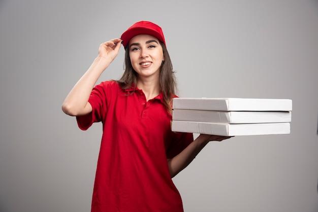 Lieferfrau, die pizzen auf grauer wand hält. Kostenlose Fotos