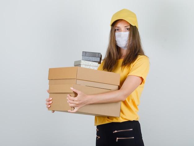 Lieferfrau hält pappe und geschenkboxen in t-shirt, hose und mütze, maske und sieht fröhlich aus Kostenlose Fotos