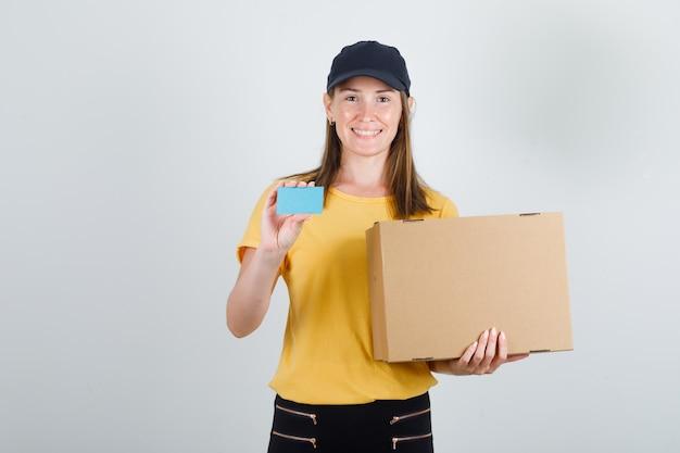 Lieferfrau hält pappkarton und blaue karte in t-shirt, hose und mütze und sieht froh aus Kostenlose Fotos
