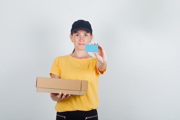 Lieferfrau hält pappkarton und blaue karte in t-shirt, hose und mütze Kostenlose Fotos