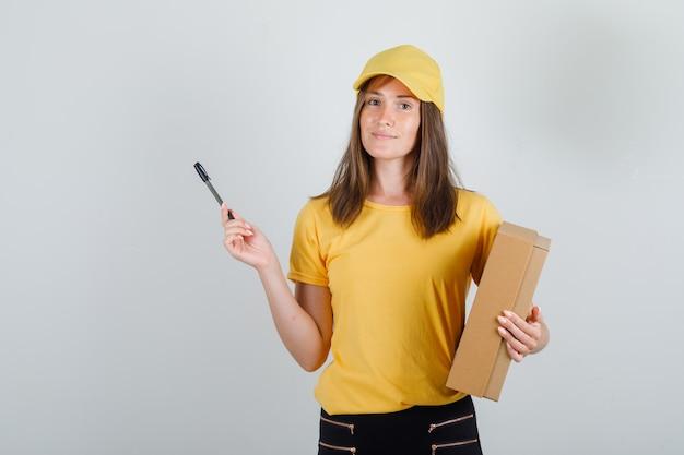 Lieferfrau hält pappkarton und stift in t-shirt, hose und mütze und sieht froh aus Kostenlose Fotos