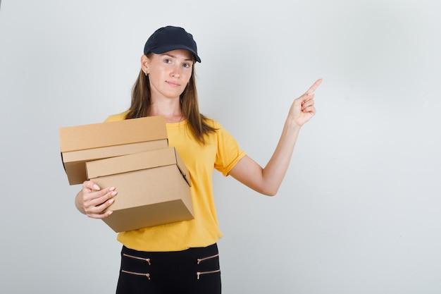 Lieferfrau hält pappkartons mit finger oben in t-shirt, hose und mütze Kostenlose Fotos