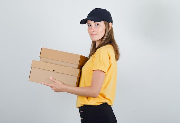 Lieferfrau hält pappkartons und lächelt in t-shirt, hose und mütze. Kostenlose Fotos