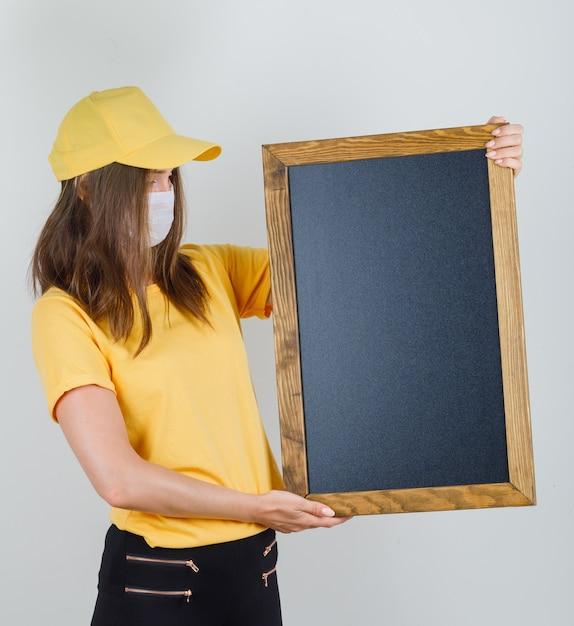 Lieferfrau hält tafel in t-shirt, hose, mütze und maske Kostenlose Fotos