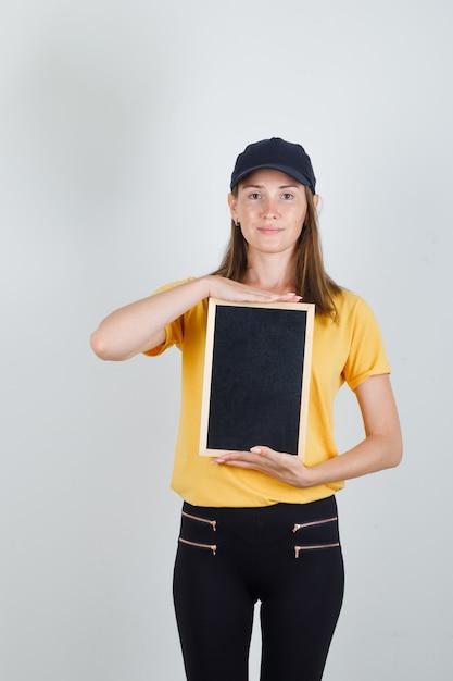 Lieferfrau hält tafel in t-shirt, hose und mütze und sieht froh aus Kostenlose Fotos