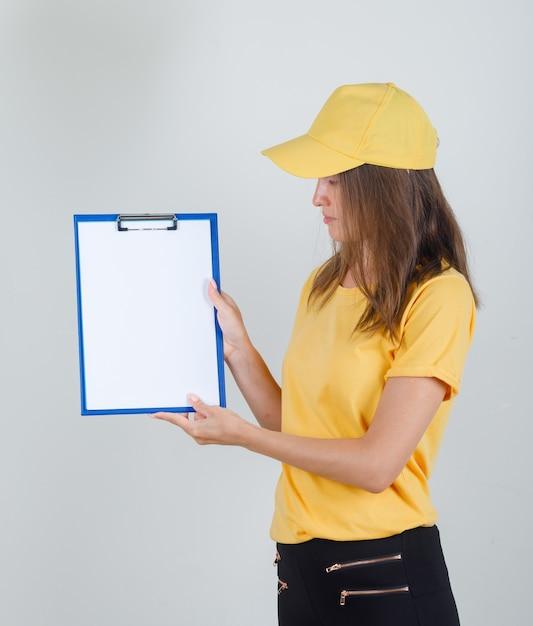Lieferfrau hält und betrachtet zwischenablage in gelbem t-shirt, hose und mütze Kostenlose Fotos