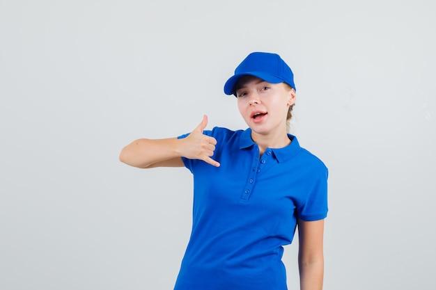 Lieferfrau im blauen t-shirt und in der kappe, die telefongeste zeigt und zuversichtlich schaut Kostenlose Fotos