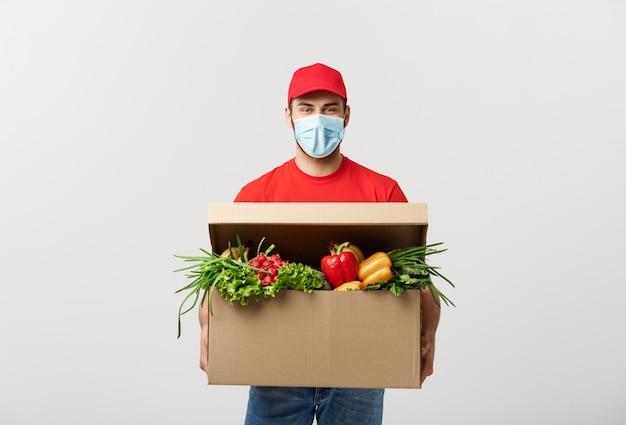 Lieferkonzept: hübscher kaukasischer kuriermann der lebensmittellieferung in roter uniform und gesichtsmaske mit einkaufsbox mit frischem obst und gemüse Premium Fotos