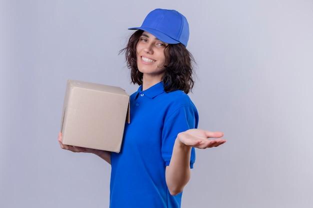 Liefermädchen in der blauen uniform und in der kappe, die boxpaket hält, das willkommensgeste mit dem lächelnden freundlichen stehen der hand macht Kostenlose Fotos