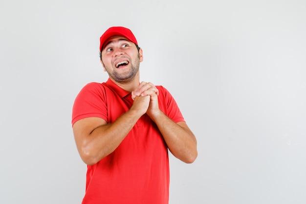 Liefermann, der hände in der gebetsgeste im roten t-shirt fasst Kostenlose Fotos