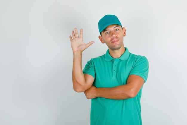 Liefermann gruß mit offener hand im grünen t-shirt mit kappe Kostenlose Fotos