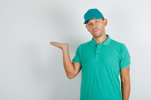 Liefermann hält geöffnete hand im grünen t-shirt und in der kappe Kostenlose Fotos