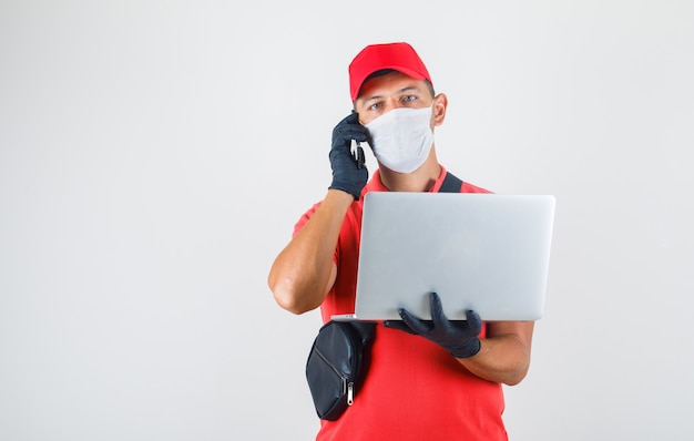 Liefermann hält laptop und spricht auf handy in roter uniform Kostenlose Fotos