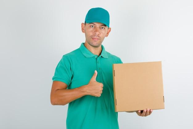 Liefermann im grünen t-shirt und in der kappe, die box hält und daumen oben zeigt Kostenlose Fotos