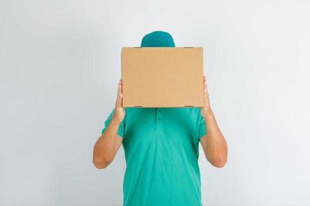Liefermann im grünen t-shirt und in der kappe, die pappkarton über gesicht halten Kostenlose Fotos