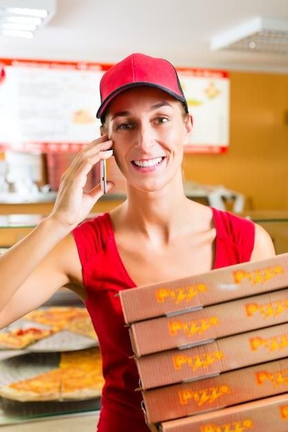 Lieferservice, frau hält pizzakartons Premium Fotos