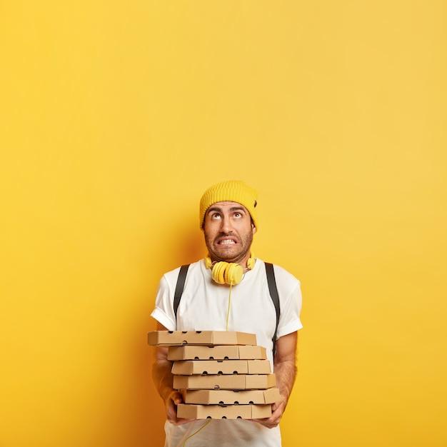 Lieferung nach hause von der pizzeria. müdigkeit mann gekleidet in freizeitkleidung, hält stapel von pappkartons, posiert mit lebensmittelbestellung. der junge pizzamann arbeitet als kurierhändler und konzentriert sich oben auf den kopierraum Kostenlose Fotos