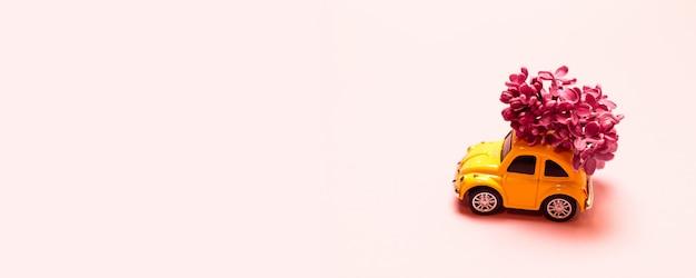 Lieferung . spielen sie gelbes auto mit lila blumenniederlassung auf einem rosa einfachen hintergrund mit platz für text. Premium Fotos