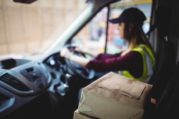Lieferungsfahrer, der packwagen mit paketen auf sitz außerhalb des lagers fährt Premium Fotos