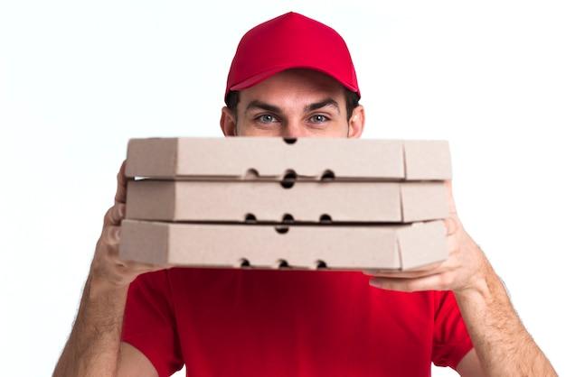 Lieferungspizzajunge, der sein gesicht mit kästen bedeckt Kostenlose Fotos