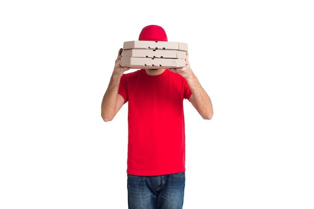Lieferungspizzajunge, der sein gesicht mit mittlerem schuss der kästen bedeckt Kostenlose Fotos
