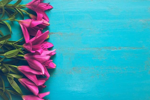 Liegerahmen der frischen gartenlilien auf altem gemaltem holztisch. schön blumig Premium Fotos