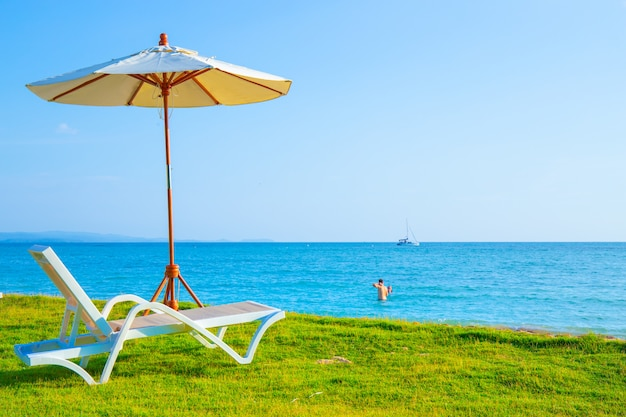 Liegestühle und sonnenschirme stehen auf der liegewiese am strand. Premium Fotos