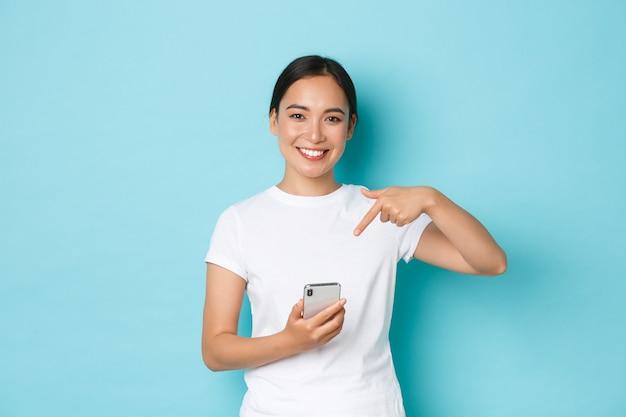 Lifestyle-, technologie- und e-commerce-konzept. taille des hübschen lächelnden asiatischen mädchens empfehlen anwendung oder einkaufsseite, handy für online-bestellung verwendend, finger auf smartphone zeigend. Premium Fotos