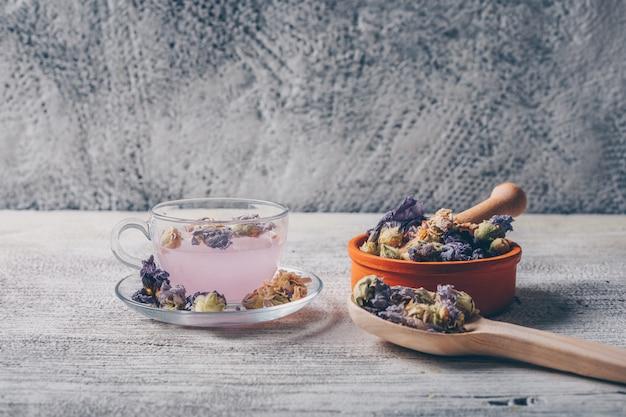 Lila gefärbtes wasser in einer tasse mit getrocknetem blumentee in einer schüssel und löffel-seitenansicht auf einem weißen hölzernen und grauen hintergrund. freier speicherplatz für ihren text Kostenlose Fotos
