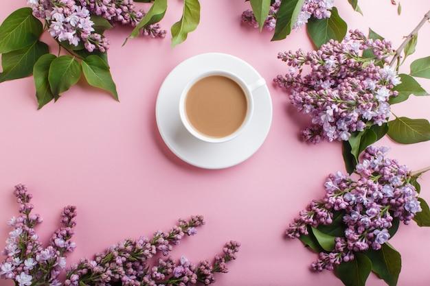 Lila lila blumen und eine tasse kaffee auf pastellrosa. Premium Fotos