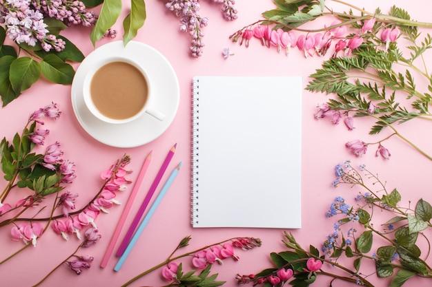 Lila lila und blutende herzblumen und ein tasse kaffee mit notizbuch und farbigen bleistiften auf pastellrosa. Premium Fotos
