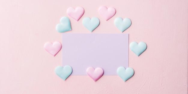 Lila pastellkarte und herzen auf rosa fahne Premium Fotos