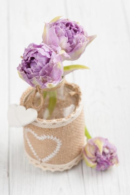 Lila tulpen in der flasche mit herzen Premium Fotos