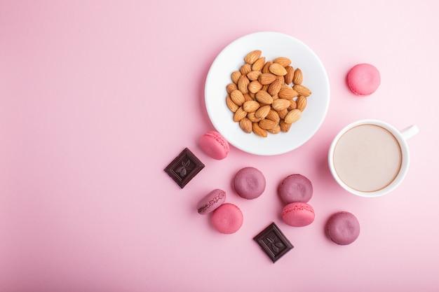 Lila und rosa macaron oder makronenkuchen mit tasse kaffee und mandeln auf pastellrosa. Premium Fotos