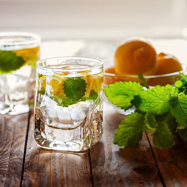 Limonade mit frischer zitrone mit zucker und minze auf hölzernem hintergrund Premium Fotos