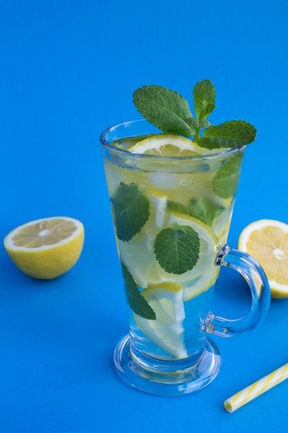 Limonade mit zitrone und minze im glas auf der blauen oberfläche Premium Fotos
