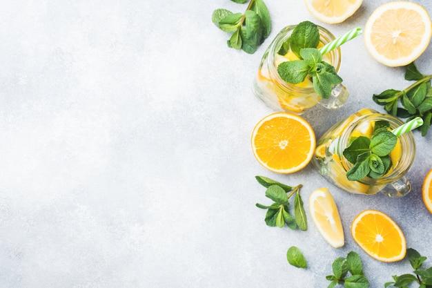 Limonadengetränk von sodawasser, zitrone und tadellosen blättern im glas auf hellem hintergrund. Premium Fotos