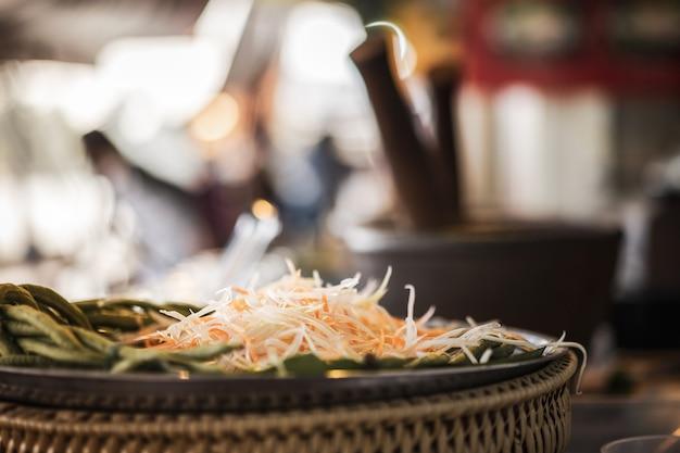 Linie papaya für papayasalatbestandteile mit unschärfemörtel. straßenlebensmittel in thailand. Premium Fotos