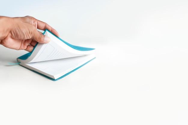 Linke hand öffnet notizbuch in einem weißen hintergrund Premium Fotos