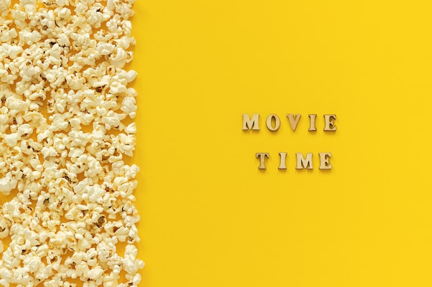 Linker rand und filmzeit des zerstreuten popcornrandes auf gelbem papierhintergrund. Premium Fotos
