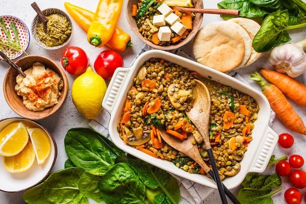 Linsencurry des strengen vegetariers mit gemüse, draufsicht. gesunde pflanzliche lebensmittel hintergrund. Premium Fotos
