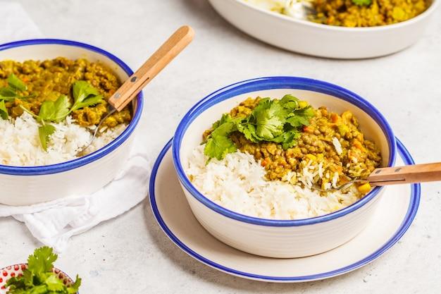 Linsencurry mit reis, indische küche, tarka dal, weißer hintergrund. veganes essen. Premium Fotos