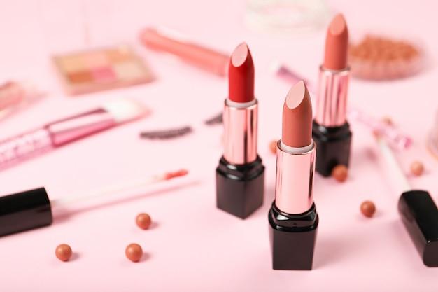Lippenstift und make-up auf einem rosa hintergrund. platz für text Premium Fotos